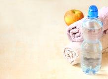Flaska av vatten och handduken arkivfoto