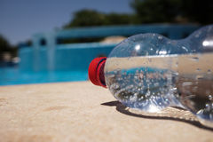 Flaska av vatten på poolside Royaltyfria Bilder
