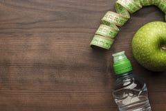 Flaska av vatten som mäter bandet och ny gräsplan Royaltyfri Bild