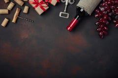 Flaska av vin, gåvaask, röda druvor, korkskruv och korkar, på rostig bakgrund arkivbilder