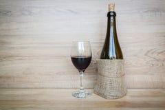 Flaska av vin och vinexponeringsglas på wood bakgrund arkivbilder
