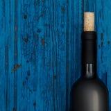 Flaska av vin på blå träbakgrund med copyspace, vin Royaltyfria Foton