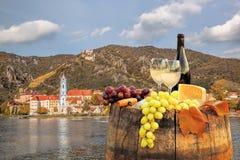 Flaska av vin på trumma med den Durnstein byn i Wachau, Österrike royaltyfri foto