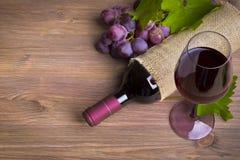 Flaska av vin, röd druva och exponeringsglas på trätabellen arkivfoton