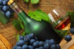 Flaska, exponeringsglas av cognacen och grupp av druvor Royaltyfri Fotografi