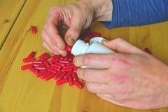 Flaska för medicin för drog för manhandinnehav som spiller piller ut ur flaskan royaltyfri foto