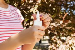 Flaska för nasala droppar, kvinnlig hand som besprutar nasal sprej med suddig bakgrund Arkivfoton