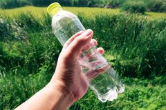 Flaska för vatten för handinnehav plast- på suddig grön trädgårdbakgrund royaltyfri fotografi