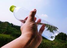Flaska för vatten för handinnehav plast- på suddig grön trädgårdbakgrund fotografering för bildbyråer