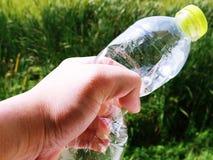 Flaska för vatten för handinnehav plast- på suddig grön trädgårdbakgrund arkivfoton