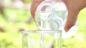 Flaska för vatten för kvinnahand hållande och hälla av klart dricksvatten in i exponeringsglaset på suddig grön naturbakgrund arkivfilmer