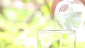 Flaska för vatten för kvinnahand hållande och hälla av klart dricksvatten in i exponeringsglaset på suddig grön naturbakgrund stock video