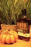 Flaska för whisky för knoppliten vikråg och orange pumpin royaltyfri foto