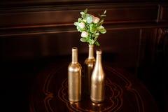 Flaska-formade vaser i guld- signal med den lilla buketten av blommor Royaltyfri Bild