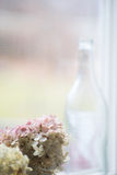 Flaska i fönster bredvid rosa blommor Arkivbilder