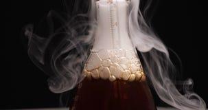 Flaska med den mörk agens och ånga i kemisk labb stock video