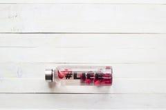 Flaska med den uppfriskande drinken, vatten med jordgubbeskivor, med hashtagliv på vit träbakgrund Royaltyfri Bild