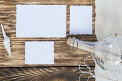 Flaska med ett meddelande i rastret på tabellen och tre tomma foto Royaltyfri Foto