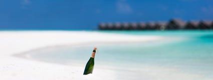 Flaska med ett meddelande på den tropiska stranden Arkivbild