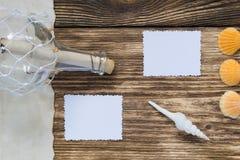 flaska med ett meddelande på tabellen och två tomma foto Arkivbilder
