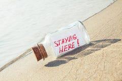 Flaska med ett meddelande som blir här på den sandiga stranden Arkivbild