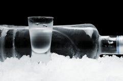 Flaska med exponeringsglas av vodka som ligger på is på svart bakgrund Royaltyfria Bilder