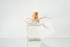 Flaska med genomskinlig flytande på den ljusa bakgrunden Royaltyfria Foton