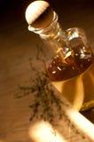 Flaska med olivolja och örter Arkivbild