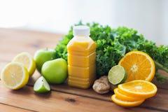 Flaska med orange fruktsaft, frukter och grönsaker Arkivbild