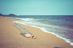 Flaska med snäckskalet på den tropiska stranden i sommar Arkivbilder