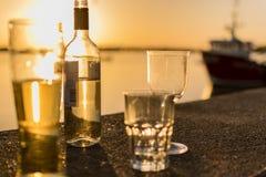 Flaska och exponeringsglas av alkohol vid havet Royaltyfri Fotografi