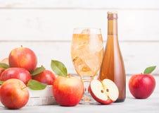 Flaska och exponeringsglas av hemlagad organisk äppelcider med nya äpplen i ask på träbakgrund med solljus arkivfoto