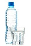 Flaska och exponeringsglas av mineralvatten som isoleras på vit Arkivbilder