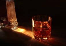 Flaska och exponeringsglas av whisky eller bourbon med is på den svarta stentabellen Arkivbilder