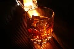 Flaska och exponeringsglas av whisky eller bourbon med is på den svarta stentabellen Royaltyfria Bilder