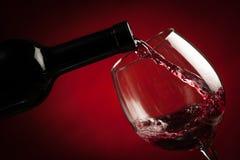 Flaska som fyller exponeringsglaset av vin Arkivbilder