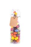Flaska som fylls med godis färgad glasyr och prislapp eller etikett fr Arkivfoton