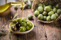Flaska som häller jungfrulig olivolja i en bunke arkivbilder