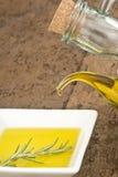 Flaska som häller jungfrulig olivolja i platta Arkivfoto