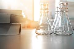 Flaska tre i vetenskapslaboratorium med boken för utbildning eller stu fotografering för bildbyråer