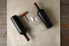 Flaska två av cabernet - sauvignon vin på en grå tegelplattayttersida på en lantlig trätabell royaltyfri fotografi