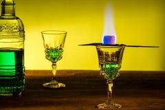 Flaskan av absint och exponeringsglas med bränning skära i tärningar farin Royaltyfri Bild