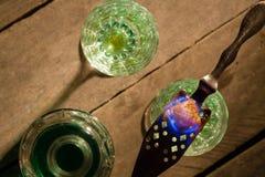 Flaskan av absint och exponeringsglas med bränning skära i tärningar farin Arkivfoto