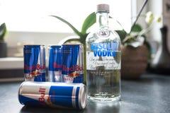 Flaskan av Absolut vodka och cans av Red Bull energi dricker på diskbänken royaltyfri bild