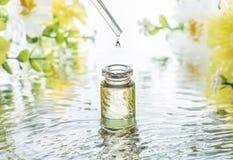 Flaskan av att fukta skönhetsmedelolja i vattenvågorna på sommarblommorna gör suddig bakgrund och pipetten med olje- droppe ovanf Arkivbild