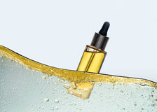 Flaskan av den gula skönhetsmedeloljan i den olje- emulsionvågen Arkivbilder