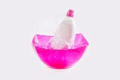 Flaskan av lokalvårdlösningen tappade in i behållarevatten med färgstänk Arkivbilder