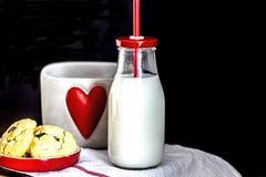 Flaskan av mjölkar och choklade kakor Arkivbilder
