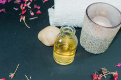 Flaskan av nödvändig olja för arom med stearinljuset, kronblad blommar Arkivbild