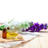 Flaskan av olja eller brunnsorten för arom nödvändig och naturlig doft oljer med blomman på trätabellen Arkivbilder